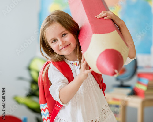 Fotografía  Little smiling blond girl holding huge red pencil in the school classroom