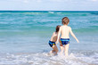 Two happy little kids boys running on the beach of ocean. Funny cute children, siblings, twins and best friends making vacations and enjoying summer on stormy sunny summer day. Miami, Florida