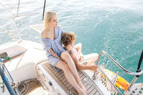 Carta da parati Sail boat during sunny summer weather on calm blue sea water with romantic couple on the deck
