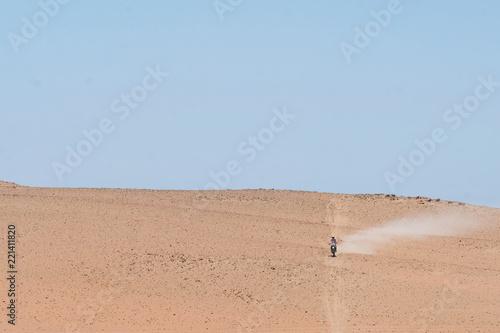 Staande foto Zandwoestijn The motorcyclist rides away in the desert. Peru, Ica