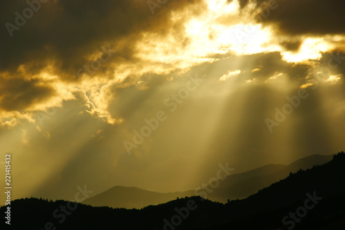 In de dag Ochtendgloren clouds with sunbeams. silhouettes of mountains and clouds at dawn