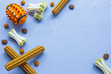 Copy Space Picture - Frame Of Dog's Stuff - Tasty Bones, Ball Toy And Feed Rolls At Beautiful Blue Background