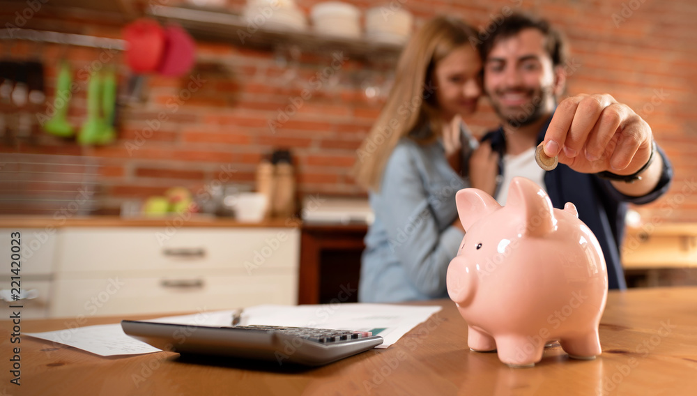 Fototapety, obrazy: Happy couple inserting coin in piggybank