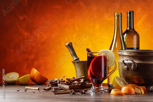 Mulled wine with spices and citrus fruits on a kitchen table with utensils.