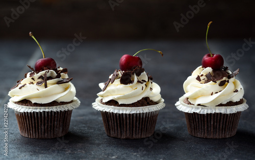 delicious sweet cupcakes decorated with cream, chocolate and fresh cherry.