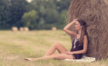 Portrait Of A Beautiful Woman With Hay Bale