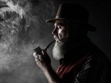 Dramatic Portrait Of Senior Man In Hat Smoking Tobacco Pipe. Profile View Of Austrian, Tyrolean, Bavarian Old Man