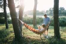Young Sympathetic Family - Mom, Dad And Son Rest In The Nature, Sitting In A Hammock