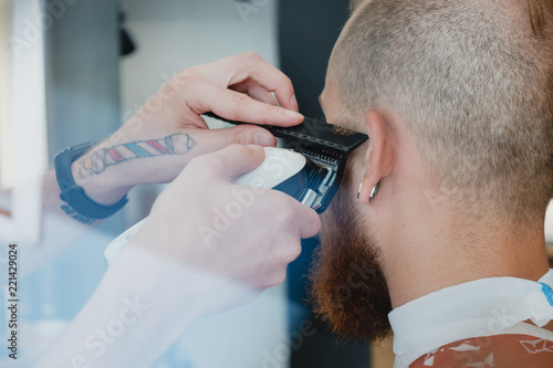 Tablou Canvas Handsome bearded bald man in barbershop