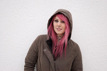 Portrait Of A Young Alternative Woman With Pink Hair Piercings And Tattoos