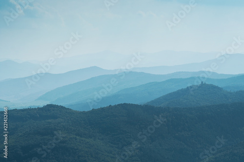 Stickers pour porte Colline Abstract blue Landscape with Silhouettes of Misty Mountains and Forest. Multilevel Mountain Range in the Background and a Dense Forest in the Foreground