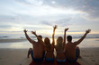 group of friends, youth sitting sunbathing on the beach / summer friends relaxing on the sea, vacation with friends on the coast tourism