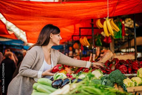 Foto Cheerful woman buying fresh vegetables farmers market.