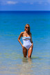 Model in white swimsuit posing at the beach
