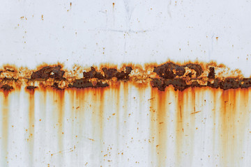 Corrosion of welding seam with red stains on a old white metal sheet. Abstrac...