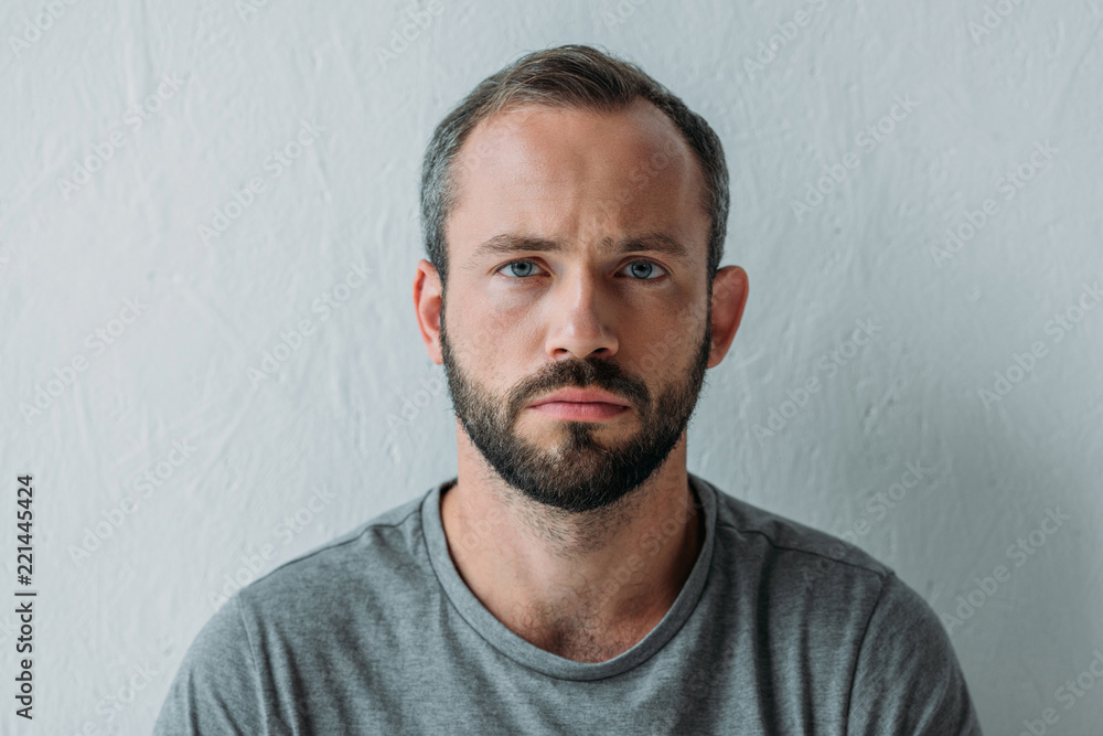 Fototapeta portrait of unhappy bearded man looking at camera on grey