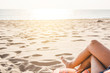 Beautiful young woman legs resting and relaxing on the beach. Sea background.Lower half of the girl body lying on the beach