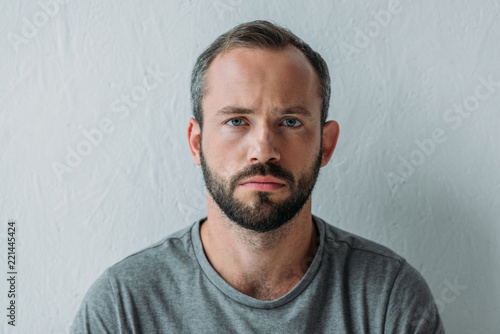 Fotografia portrait of unhappy bearded man looking at camera on grey