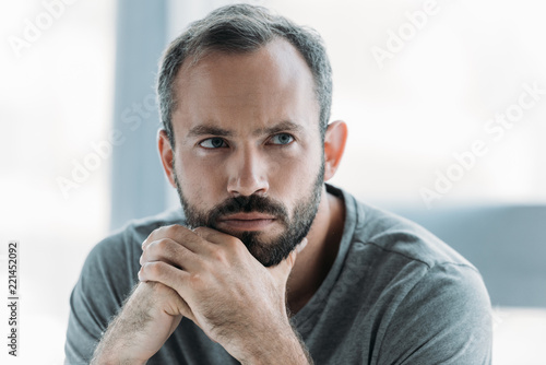 portrait of unhappy bearded middle aged man with hands on chin looking away