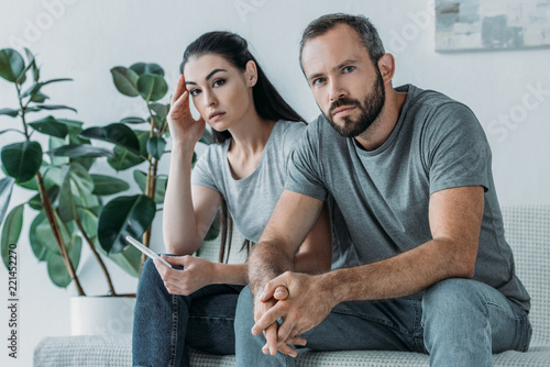 Fotomural sad stressed couple with pregnancy test sitting and looking at camera