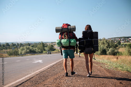 Travel man hitchhiking. Backpacker on road Canvas Print