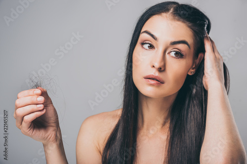 young brunette woman holding fallen hair and looking away isolated on grey, hair loss concept