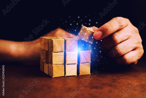 Fotografie, Obraz  business man try to build wood block on wooden table and blur background busines