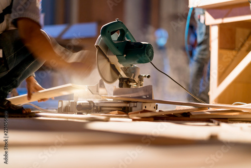 Obraz na plátně  home improvement ideas concept with carpenter work with sawing wood machine site