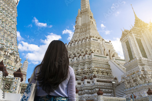 Woman tourist is looking at the Pagoda inside Wat Arun temple in Bangkok, Thailand during holiday vacation time.