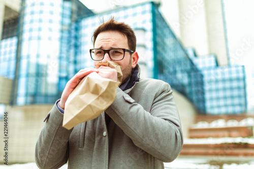 Obraz na płótnie Businessman holding paper bag over mouth as if having a panic attack