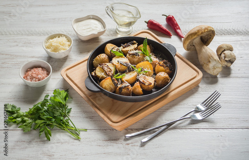 Country potatoes with fried mushrooms on a cast iron pan.