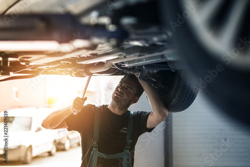 Car mechanic repairing vehicle using wrench tool in his workshop.