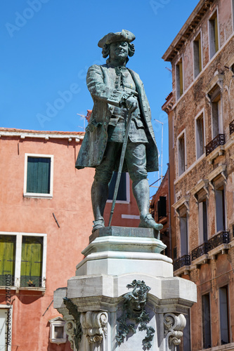 Deurstickers Historisch mon. Playwright Carlo Goldoni statue with pedestal by Antonio Dal Zotto (1841-1918) in Venice, clear blue sky in Italy