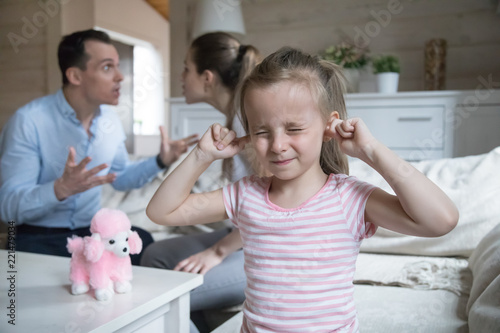 Little girl close ears refuse to listen to parents fighting