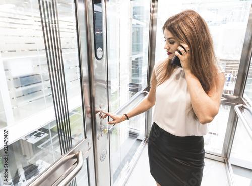 Fototapeta woman pressing elevator button. finger presses elevator button. businessman in lift obraz