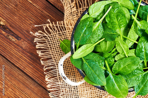 Fresh spinach leaves in a wooden background