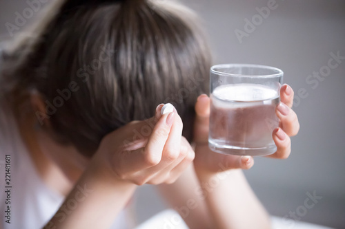 Photo Sick frustrated woman feel unwell holding glass of water and pill doubting to ta