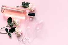 White Roses, Wine And Glasses For Wine On A Soft Light Pink On Wood Table. Flat Lay, Top View, Copy Space
