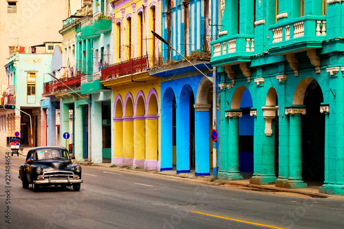 Photo Street scene with old classic car and colorful buildings in Havana