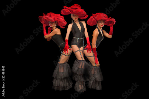 Fotografia, Obraz Three beautiful cabaret dancers in red hats isolated on black
