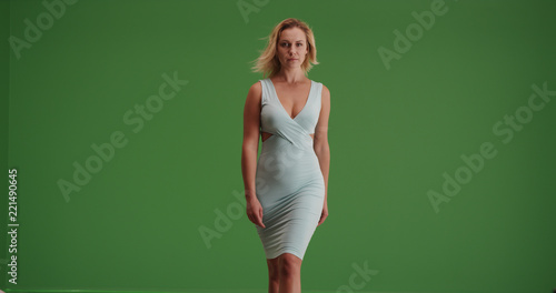 Fotografia  Caucasian woman in a teal dress walking toward the camera on green screen