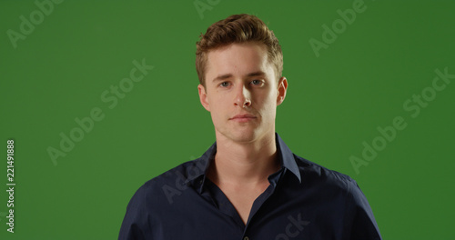 Cuadros en Lienzo Handsome young Caucasian man looking at camera on green screen
