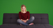 canvas print picture - Casual young blonde woman sitting on sofa smiling on green screen
