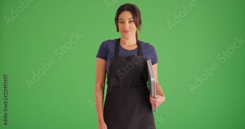 Stampa su Tela Smiling Hispanic woman wearing apron posing with baking sheet on green screen