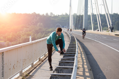 Fotografía  Jogger tying laces on bridge