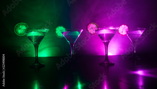 Several glasses of famous cocktail Martini, shot at a bar with dark toned foggy background and disco lights. Club drink concept.