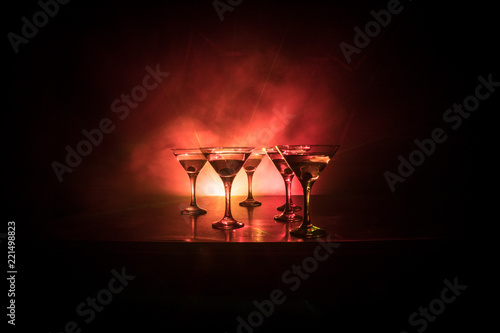 Several glasses of famous cocktail Martini, shot at a bar with dark toned foggy background and disco lights. Club drink concept