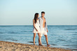 Happy young couple walking together on beach