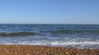 Sea waves and pebble beach on a sunny day. Britain.