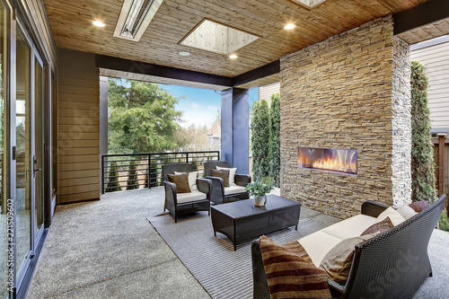 Stampa su Tela Luxury modern deck exterior with stone fireplace and wooden ceiling